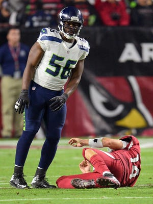 Seahawks defensive end Cliff Avril (56) stands over Cardinals quarterback Ryan Lindley (14) after a first-half hit.