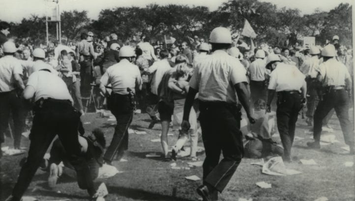 Chicago police officers charge through a crowd of demonstrators