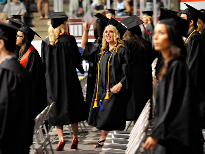 A student waves as she finds her family and friends during the processional for the morning commencement ceremony at St. Cloud State University Students Sunday, May 11.