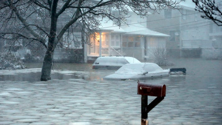 Water floods a street in coastal Scituate, Mass., after