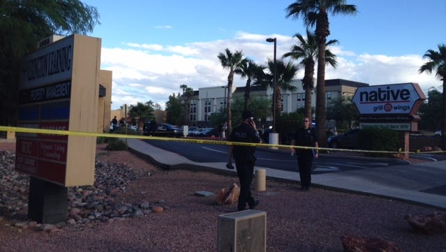 Police tape lines a plaza in Mesa where officers shot a suspect under investigation by the ATF.