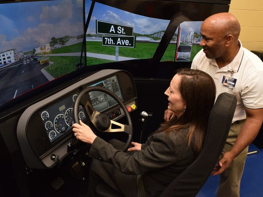 Ramon Milano (right), an instructor for the Commerical Driver's License program at Central Louisiana Technical Community College, guides Valerie Aymond, chief resource officer at Gilchrist Construction Company, as she drives the new truck driving simulator at CLTCC.