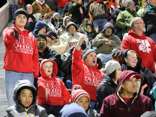 """Redskins fans do the """"tomahawk chop"""" as their team takes the field in Tiffin for a playoff game against Columbus Bishop Hartley."""