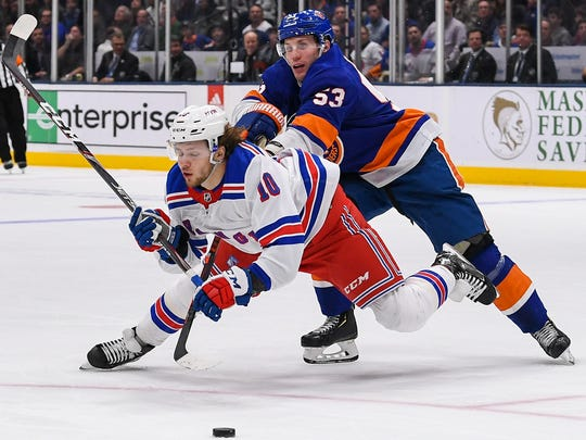 Jan 16, 2020; Uniondale, New York, USA; New York Islanders center Casey Cizikas (53) checks New York Rangers left wing Artemi Panarin (10) during the third period at Nassau Veterans Memorial Coliseum. Mandatory Credit: Dennis Schneidler-USA TODAY Sports