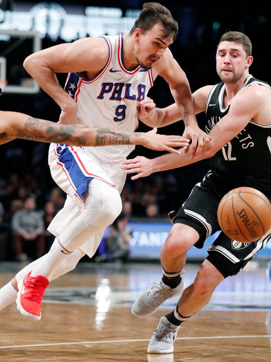 Philadelphia 76ers forward Dario Saric (9) and Brooklyn Nets forward Joe Harris (12) chase a loose ball down court during the first half of an NBA basketball game, Sunday, March 11, 2018, in New York. (AP Photo/Kathy Willens)