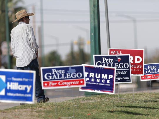 A man walks past campaign signs which line the sidewalk outside the Pavo Real Recreation Center early voting site Monday. Record numbers of voters continue in El Paso.