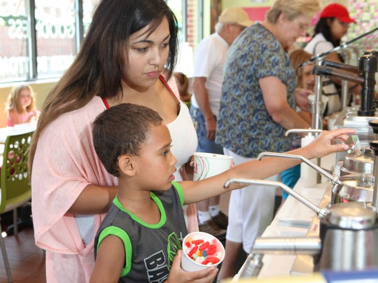 Gabby Morano, and Aiden Warren, of the Town of Poughkeepsie pick out toppings at Hoopla Frozen Yogurt in the Town of Poughkeepsie on Wednesday. Morano and Warren spent the afternoon seeking some relief from the heat by getting frozen yogurt.