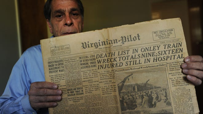 Mark Williams holds a copy of the Monday, Dec. 2, 1929 edition of the Virginian-Pilot with a story detailing a train wreck in Onley, Va. that killed nine people and injured 20 others.