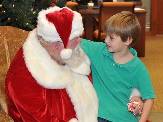 Eight-year-old Shane Rater takes his turn in Santa Claus' lap Thursday afternoon in the lobby of the First National Bank located at Fairway Boulevard at Kell Freeway. Jan Waldmuller of First National Bank said parents and grandparents were encouraged to bring phones and cameras to capture memories of the event.