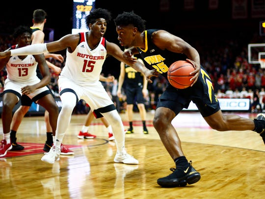 Iowa forward Tyler Cook (25) drives to the basket past Rutgers center Myles Johnson (15) during the first half of an NCAA college basketball game Saturday, Feb. 16, 2019, in Piscataway, N.J. (AP Photo/Adam Hunger)