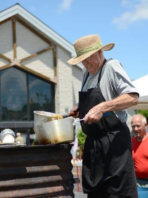 RIGHT: Fran DeCleene serves booyah, a food staple at area church picnics.