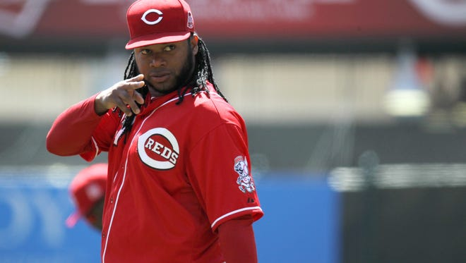 Reds starting pitcher Johnny Cueto points to the dugout on April 11.