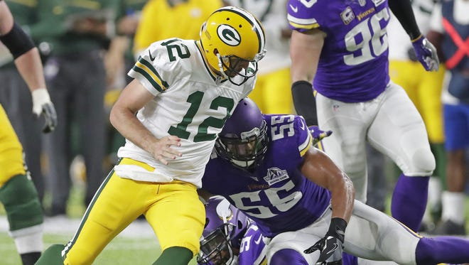 Green Bay Packers quarterback Aaron Rodgers (12) tries to recover his fumble after being stripped on a scramble against the Minnesota Vikings outside linebacker Anthony Barr (55) at U.S. Bank Stadium on Sept. 18, 2016.