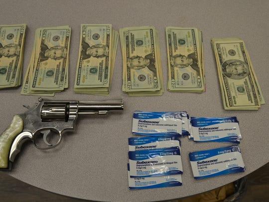 A gun, cash and Suboxone strips were found in a storage