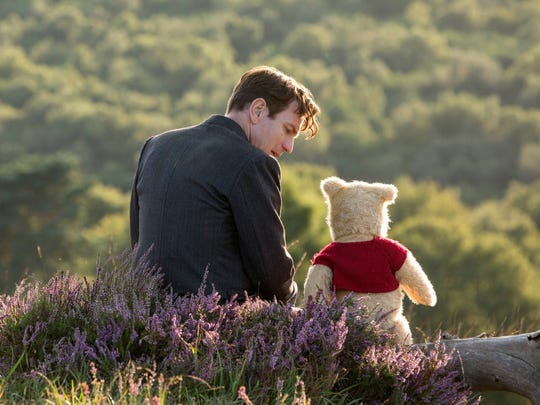 Ewan McGregor, as Christopher Robin, sits with Winnie