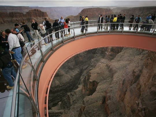 Visitors step onto the Grand Canyon Skywalk on opening