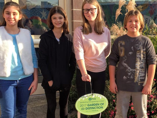 Readington Middle School teacher Denise Birmingham, who is the school's Garden Club advisor, accepted the award at a reception hosted by the Pennsylvania Horticultural Society in Philadelphia on November 14.  In the photo, Garden Club members Ellie Mahlis, Sara Borella, Jenna Dambres, and Juergen Rau proudly display the sign that was presented to  Birmingham.