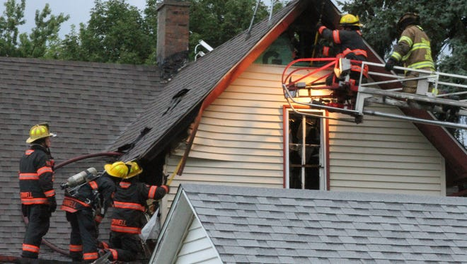 Firefighters with the Grinnell and Gilman fire departments look for hot spots at a residential fire at 1119 Spring St., Grinnell which was caused by a lightning strike early on Monday, Aug. 6.