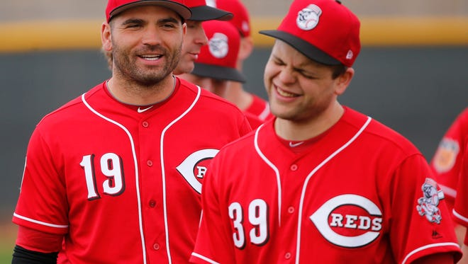 Cincinnati Reds first baseman Joey Votto (19) and Cincinnati Reds catcher Devin Mesoraco (39) share a light while warming up during Cincinnati Reds spring training, Friday, Feb. 17, 2017, at the Cincinnati Reds player development complex in Goodyear, Arizona.