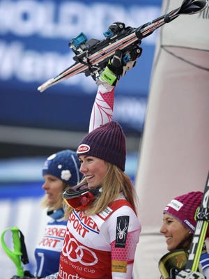 Mikaela Shiffrin, of the United States, center, raises her skis as she celebrates her first place in the alpine skiing women's World Cup slalom in Killington, Vt., Sunday, Nov. 27, 2016. With Shiffrin are second place winner Veronika Velez Zuzulova, of Slovenia, left, and third place winner Wendy Holdener, of Switzerland, right.