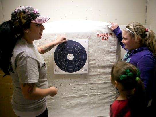 Kam Fehrenbach of Saratoga, left, puts up a new target