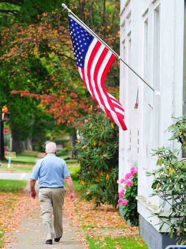 A pedestrian walks down a street in Warren, PA September, 30, 2014.