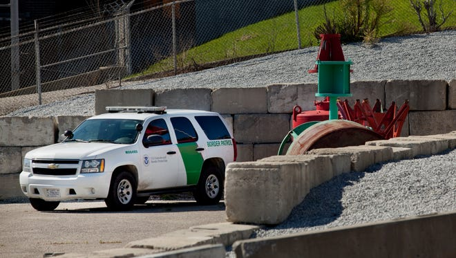 A U.S. Customs and Border Protection patrol officer keeps watch from their vehicle September 26, 2014 at the Bean Dock on the St. Clair River in Port Huron.