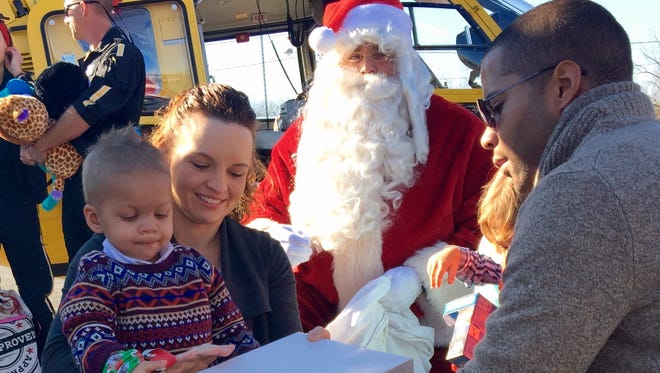 Brady Kier, 2, opens gifts Santa brought to him on Saturday. Santa made a special trip to Staunton in a helicopter to see the little boy who is fighting cancer.