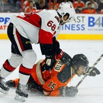 Ottawa Senators' Mike Hoffman, puts Philadelphia Flyers' Michael Del Zotto down on the ice in the second period of an NHL hockey game against the Philadelphia Flyers, Saturday, April 11, 2015, in Philadelphia. The Senators won 3-1.