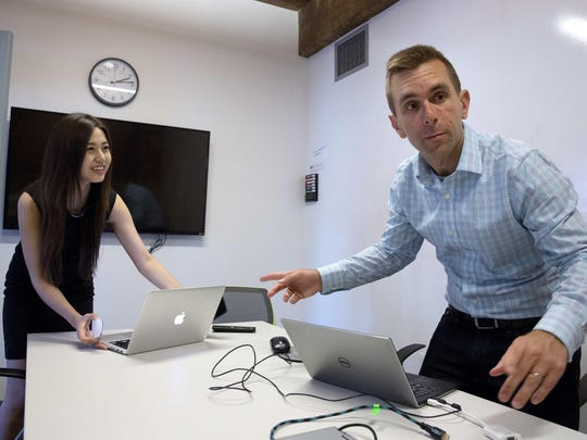Todd Horton, right, and his intern Minjee Kim, of Seoul, prepare for a Skype connection in a conference room at a co-work space in Arlington, Massachusetts. At Horton's human resources software company, KangoGift, four staffers work together in Boston and six are remote, scattered in Europe and India.