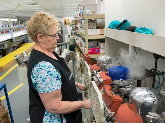 roduction operator Gail Zabawa steams and presses a