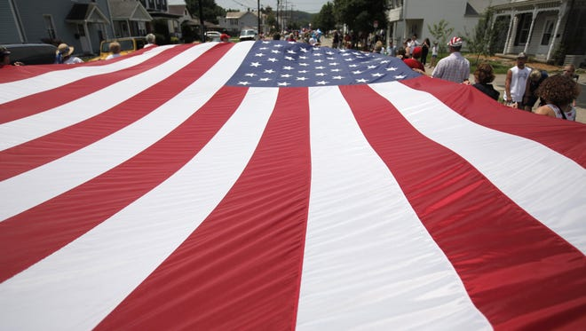 Members of the Harrison Historical Society carry a giant American flag during the 2011 Fourth of July celebration.