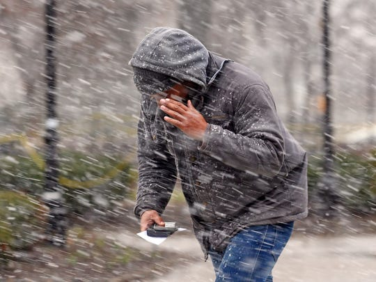 A man braces himself from heavy winds as he crosses The Green in Morristown. braving the elements as a nor'easter dropping heavy rain and snow bears down on the Northeast. March 2, 2018. Morristown, NJ.