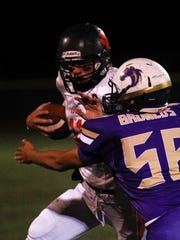 Aztec quarterback Cody Smith stiff arms Kirtland Central tackler Jonathan Arreola during an Oct. 6 game at Bronco Stadium in Kirtland.