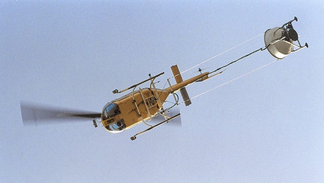 A helicopter dumps pellets on Rosewood Golf Course Thursday morning May 15, 2003 in an effort to help rid the area of mosquitoes.
