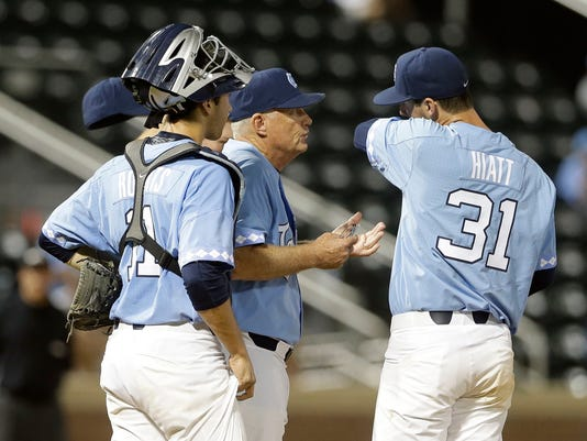 North Carolina coach Mike Fox speaks with pitcher Josh Hiatt (31) and catcher Cody Roberts (11) during the seventh inning of an NCAA college baseball tournament regional game against Davidson in Chapel Hill, N.C., Sunday, June 4, 2017. (AP Photo/Gerry Broome)