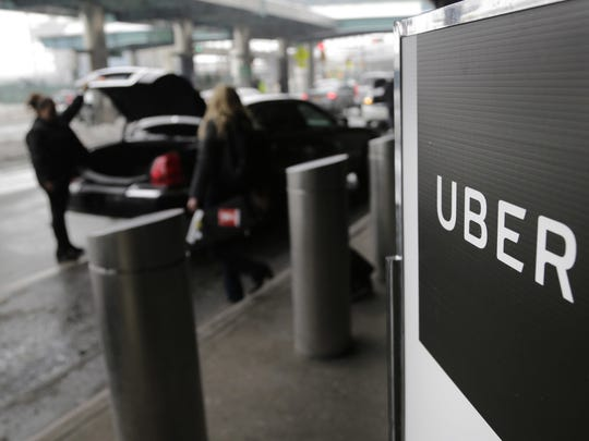 FILE - In this March 15, 2017, file photo, a sign marks a pick-up point for the Uber car service at LaGuardia Airport in New York. Drivers for ride-hailing giants Uber and Lyft are planning to turn off their apps to protest what they say are declining wages at a time when both companies are raking in billions of dollars from investors. (AP Photo/Seth Wenig, File)