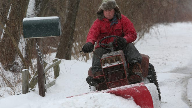 Ethan Gallagher uses a tractor and plow to clear about 5 inches of snow in Philipstown Jan. 27, 2015. Snow accumulation was much less than expected after a major storm tracked about 50 miles east of it's predicted path.