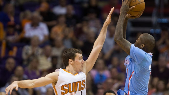Suns' Goran Dragic defends Clippers' Jamal Crawford as he makes a three point basket at US Airways Center in Phoenix, AZ on January 25, 2015.