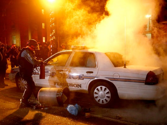 Police douse a burning patrol car after protesters