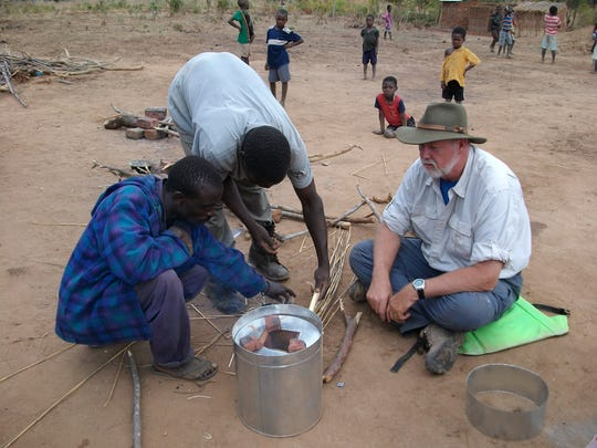 North Central State College assistant professor of engineering Ken Ekegren is shown here in Malawi, Africa, with one of the cook stoves he and three of his College NOW students hope to improve in design for villagers when they visit the country in January.