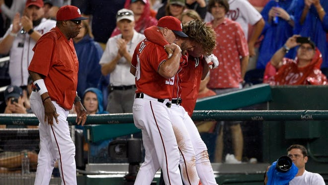 Washington Nationals right fielder Bryce Harper is helped off the field after appearing to injure his knee.