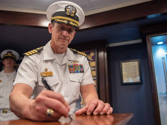 SAN DIEGO (August 3, 2018) Capt. Greg Huffman signs a replica Senate desk, a tradition among commanding officers of the Nimitz-class aircraft carrier USS John C. Stennis (CVN 74), in the John C. Stennis Museum following a change of command ceremony.