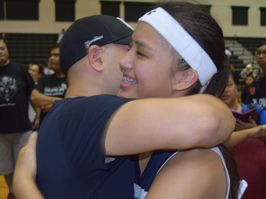 St. Paul Christian Warriors junior center Joniah Siguenza hugs head coach Paul Pineda after the Warriors victory over the Academy of Our Lady of Guam Cougars. The Warriors beat the Cougars 56-54 in overtime on Siguenza's last-second bucket to claim the Independent Interscholastic Athletic Association of Guam's High School League championship match on Saturday, December 9 at the University of Guam Calvo Field House.