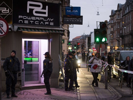 Armed police stand guard outside an Internet cafe that