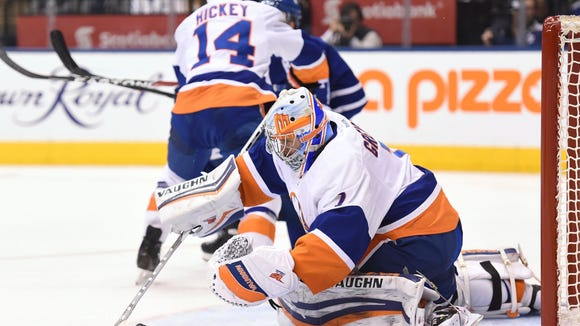 New York Islanders goalie Thomas Greiss (1) covers the puck after making a save against the Toronto Maple Leafs during second period NHL hockey action in Toronto on Tuesday, Feb. 14, 2017. (Frank Gunn/The Canadian Press via AP)