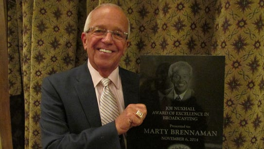 Marty Brennaman holding the Joe Nuxhall Award for Excellence