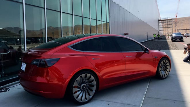 A Tesla Model 3 sedan, due to begin production next year, is shown outside the company's massive Gigafactory east of Reno, Nev.