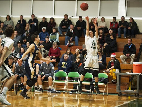 Rice's Elliott Nelson (20) takes a 3-point shot during the boys basketball game between the Essex Hornets and the Rice Green Knights in December.
