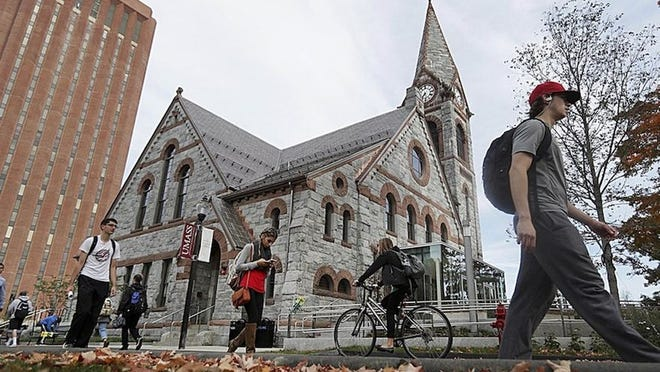 Students pass the Old Chapel at the University of Massachusetts campus in Amherst. Those who return to campus this fall will be required to wear face masks, social distance and subject to regular COVID-19 testing.